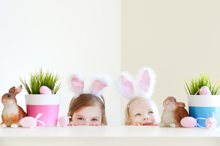in ear: Dos peque�as hermanas adorables que llevan orejas de conejo el d�a de Pascua Foto de archivo