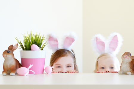Two adorable little sisters wearing bunny ears on Easter day 스톡 콘텐츠