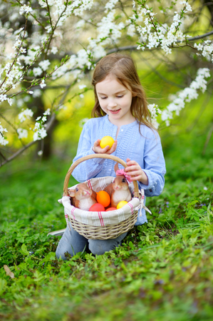 Adorable little girl holding a basket of Easter eggs in blooming spring garden on Easter day photo