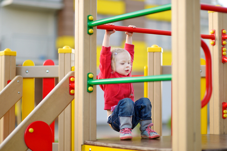 playground equipment: Little toddler girl having fun at a playground