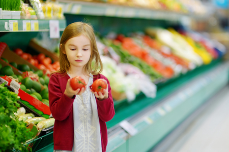 healthy choices: Little girl choosing tomatoes in a food store