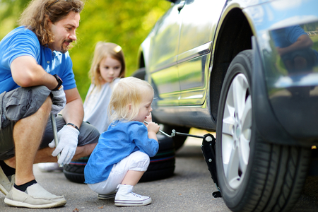 Adorable little girl helping her father to change a car wheel outdoors on beautiful summer day photo
