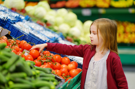 Little girl choosing tomatoes in a food store