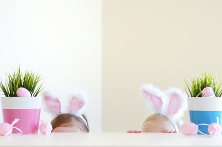 huevo blanco: Dos peque�as hermanas adorables que llevan orejas de conejo el d�a de Pascua Foto de archivo