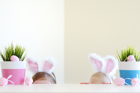 egg white: Two adorable little sisters wearing bunny ears on Easter day Stock Photo