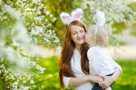 bunny ears: Young mother and her daughter wearing bunny ears in a spring garden on Easter day