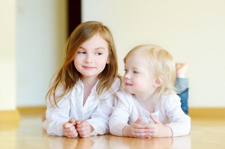 girl lying: Portrait of two cute sisters at home Stock Photo