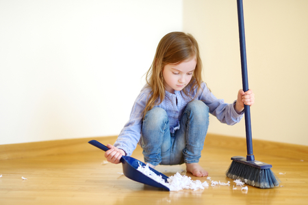 Adorable little girl helping her mom to clean up at home 写真素材