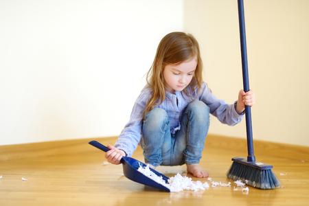 Schattig klein meisje helpt haar moeder op te ruimen thuis
