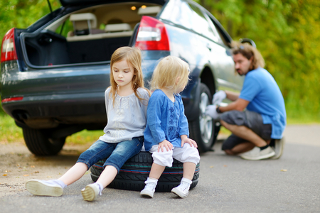 Two adorable little sisters sitting on a tire and waiting while their father is changing a car wheel outdoors on beautiful summer day photo