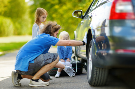 Young father and his two daughters changing a car wheel outdoors on beautiful summer day photo