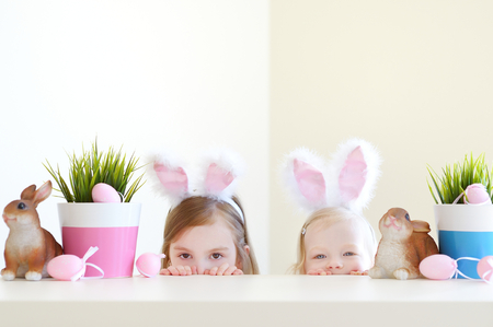 easter flowers: Two adorable little sisters wearing bunny ears on Easter day Stock Photo