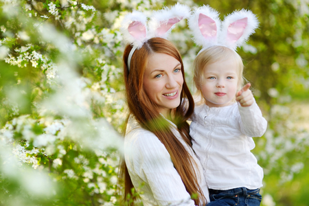 osterhase: Junge Mutter und ihre Tochter tragen Häschenohren in einem Frühlingsgarten am Ostersonntag