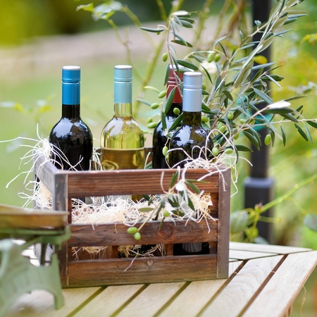cabarnet: Wine bottle in a vintage wooden crate decorated with olive branches