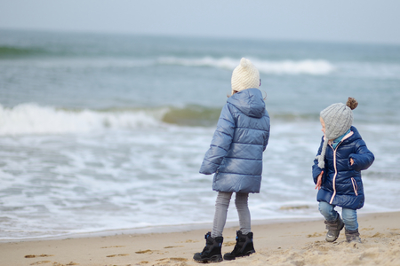 Adorable little sisters playing by the ocean on cold winter day photo