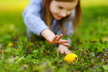 Adorable little girl hunting for easter egg in blooming spring garden on Easter day