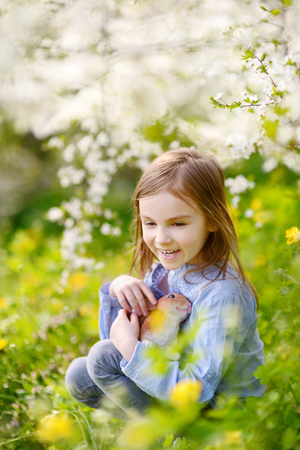 Adorable little girl in blooming cherry garden holding easter bunny on beautiful spring day photo