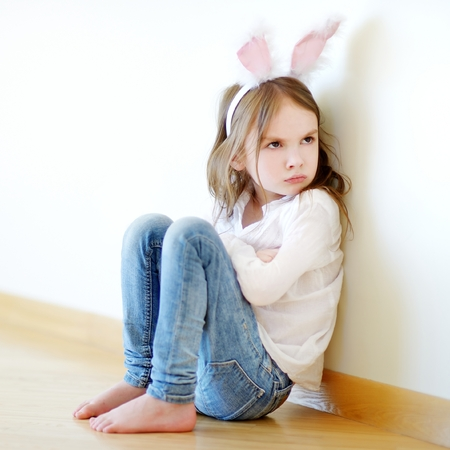 children face: Very angry little girl wearing bunny ears sitting on a floor at home Stock Photo