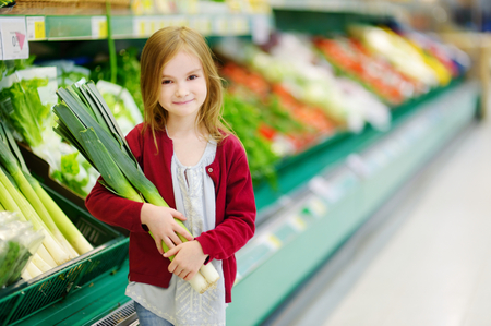produce departments: Little girl choosing a leek in a food store Stock Photo
