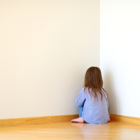 Very sad little girl sitting on a floor at home photo