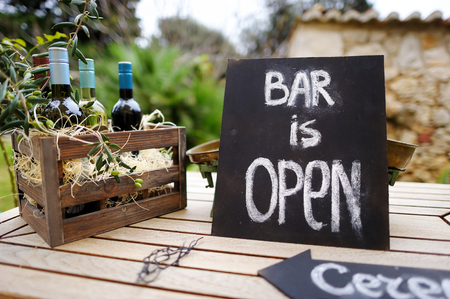 ceremonia: Bar es señal abierta y la caja de madera de época llena de botellas de vino adornado con ramas de olivo en una mesa