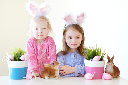 bunny ears: Two adorable little sisters wearing bunny ears on Easter day Stock Photo