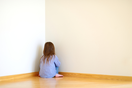 Very sad little girl sitting on a floor at home