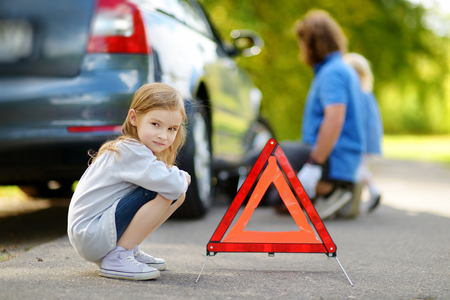 road to change: Adorable little girl waiting by the red warning triangle sign while her father is changing a car wheel outdoors on beautiful summer day