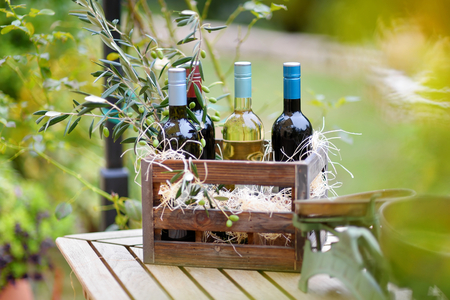 bordeau: Wine bottle in a vintage wooden crate decorated with olive branches
