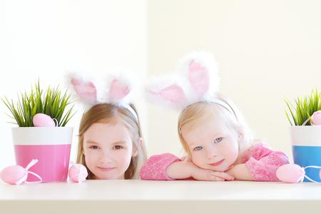 huevos de pascua: Dos peque�as hermanas adorables que llevan orejas de conejo el d�a de Pascua Foto de archivo