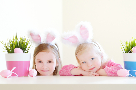Two adorable little sisters wearing bunny ears on Easter day Stock Photo