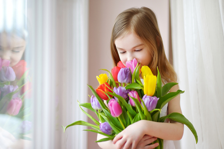 romantic flowers: Adorable smiling little girl holding tulips by the window