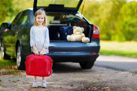 Adorable little girl with a suitcase leaving for a car vacation with her parents Banco de Imagens - 41201987