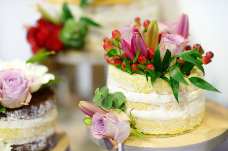 White wedding cake decorated with natural flowers photo