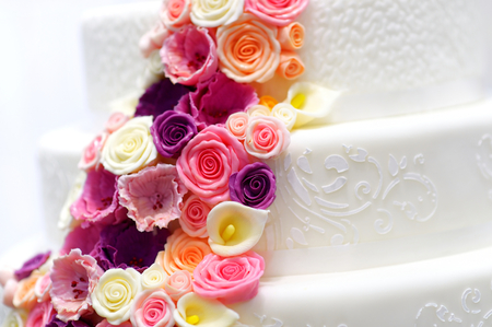 wedding table decor: Detail of a white wedding cake decorated with pink sugar flowers