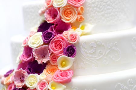 pastel boda: Detalle de un pastel de boda blanco decorado con flores rosadas de azúcar Foto de archivo
