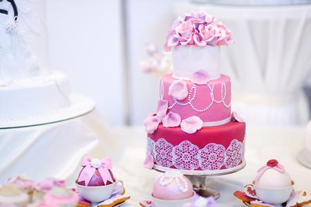 Vit bröllopstårta dekorerad med rosa socker blommor