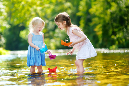 Two little sisters playing with paper boats by a river on warm and sunny summer day Stock Photo