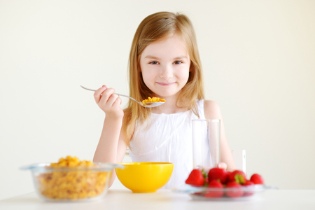 comiendo cereal: Adorable little girl eating cereal with strawberries and drinking milk in white kitchen Foto de archivo