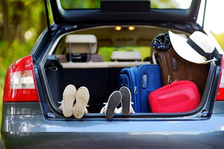 riendo: Dos peque�as hermanas adorables que se sientan en un coche justo antes de salir para un coche vacaciones con sus padres