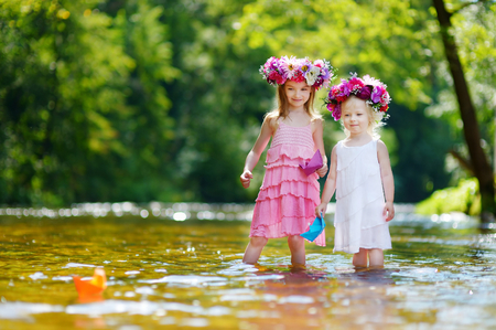 Two adorable little sisters wearing flower crowns playing with paper boats by a river on warm and sunny summer day
