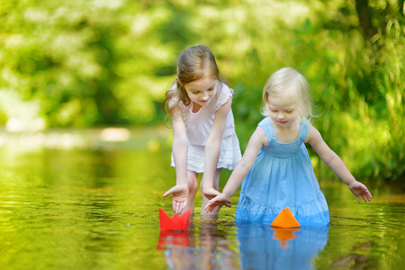 sunny day: Two little sisters playing with paper boats by a river on warm and sunny summer day Stock Photo