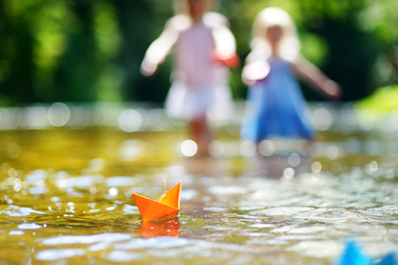 children pond: Two little sisters playing with paper boats by a river on warm and sunny summer day Stock Photo
