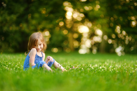 green garden: Cute little girl sitting on the grass on a sunny summer day