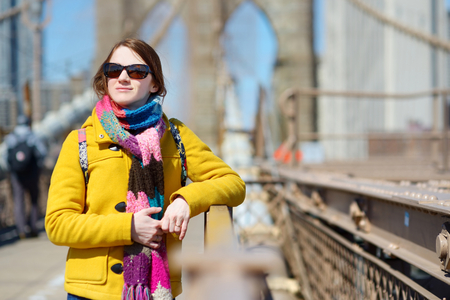 Beautiful young woman sightseeing on Brooklyn Bridge, New York, at sunny spring day photo