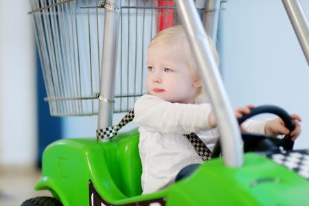 family mart: Adorable little girl sitting in shopping cart