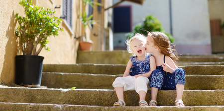 familias jovenes: Two cute little sisters sitting on stairs in italian town