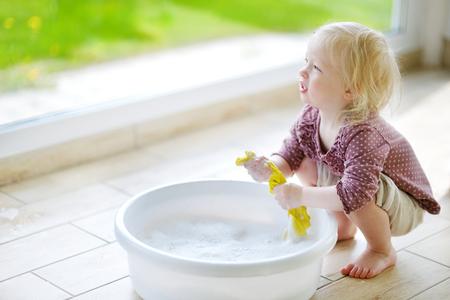 Kleine peuter meisje helpt haar moeder op te ruimen op lentedag Stockfoto