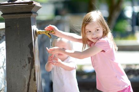 tomando agua: Dos hermanas que se divierten con la fuente de agua potable en Italia
