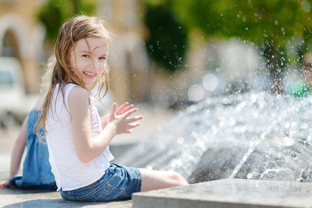 summer fun: Cute little preschooler girl playing with a city fountain on hot and sunny summer day